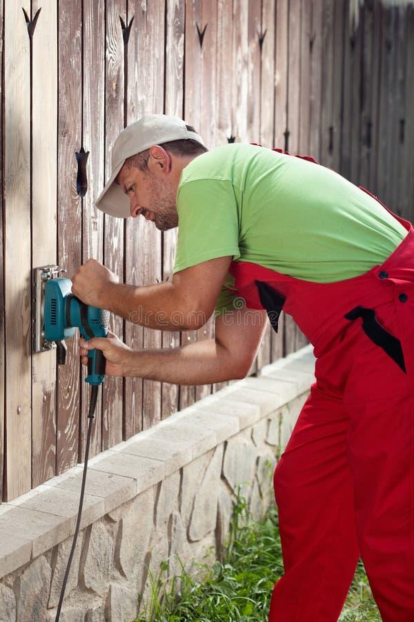 Man refurbishing old wooden fence royalty free stock image