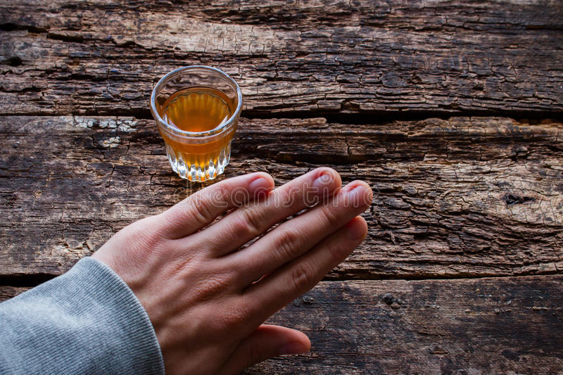 Man refuses alcohol on table. Man refuses alcohol on wooden background royalty free stock images