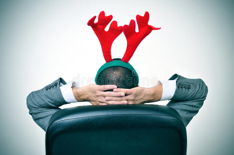 Man with a reindeer antlers headband in his office chair. A man with a reindeer antlers headband relaxing in his office chair after an office christmas party royalty free stock images