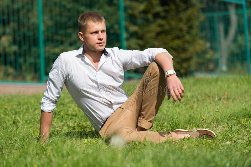 Man relax on green grass. Businessman in shirt and pants on sunny outdoor. Handsome macho enjoy summer day. Fashion royalty free stock photo