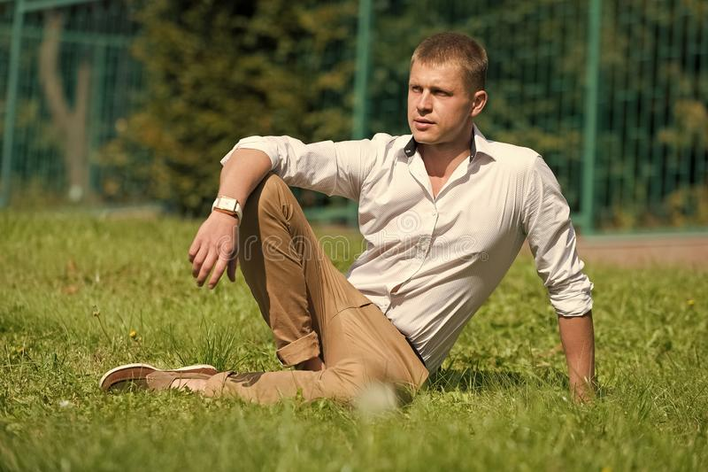 Man relax on green grass. Businessman in shirt and pants on sunny outdoor. Handsome macho enjoy summer day. Fashion royalty free stock photography