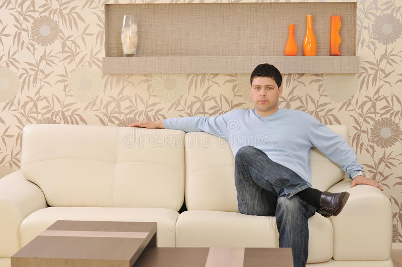 Man relax at home. One happy young man relax at home in livingroom with modern style furniture indoor royalty free stock photos