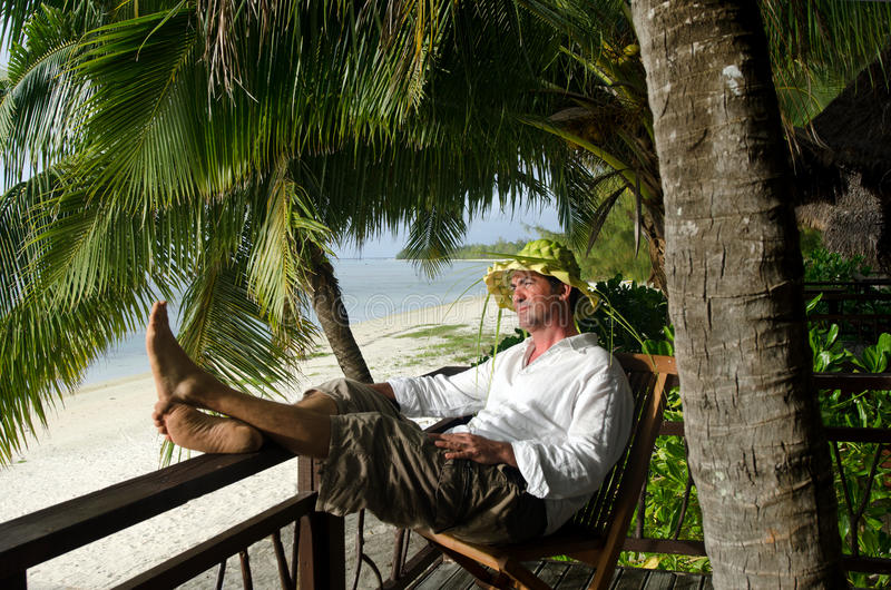 Man relax during travel vacation on tropical islan. Successful man in his 40s relax during travel vacation on tropical island in Aitutaki lagoon, Cook Islands royalty free stock photo