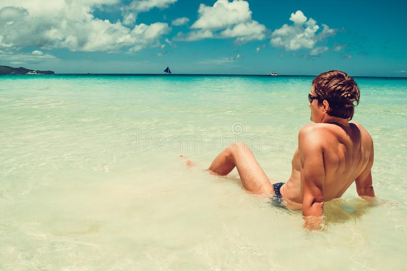Man relax in water enjoying summer beach vacation. Time to travel. Stress free. Shirtless fit athletic male body. Exotic luxury ho stock photo
