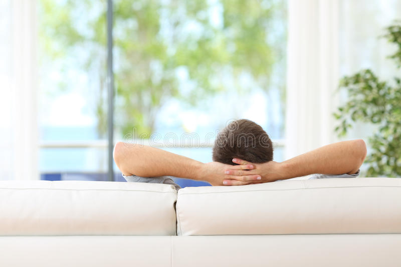 Man relaxed on a couch at home stock images