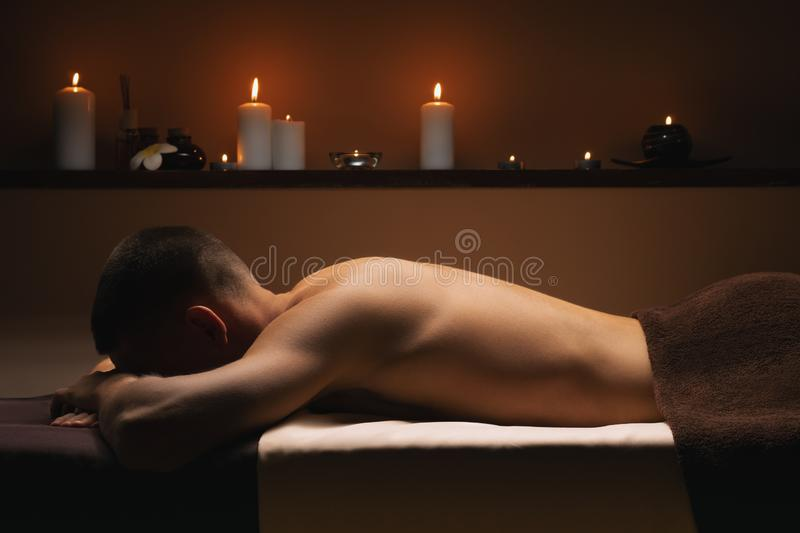 Man relaxes at SPA. Calm, pacifying atmosphere around. Beautiful background, candles, charming light royalty free stock photos