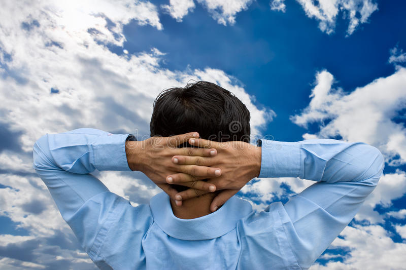 Man relaxing. With his hands behind his head royalty free stock photos