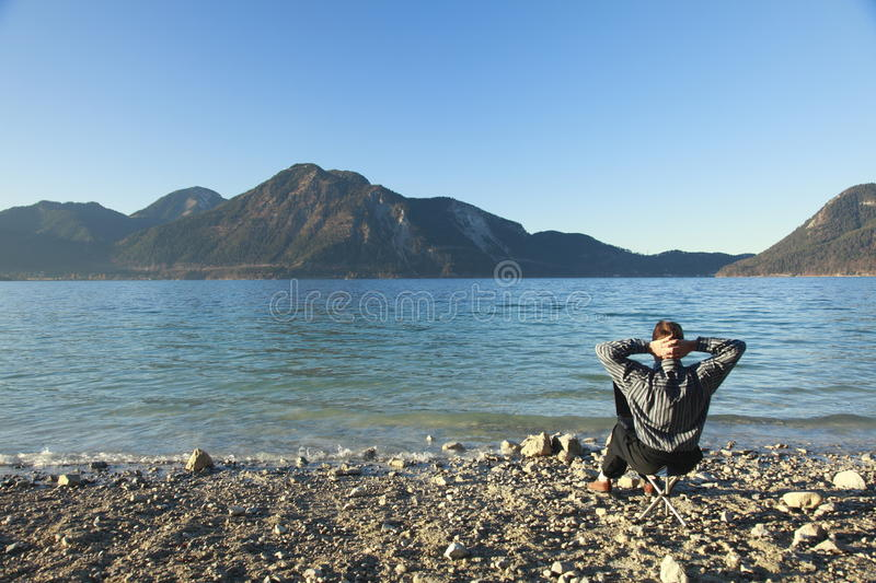 Man is relaxing. Business man on chair in nature,lake in background royalty free stock photography