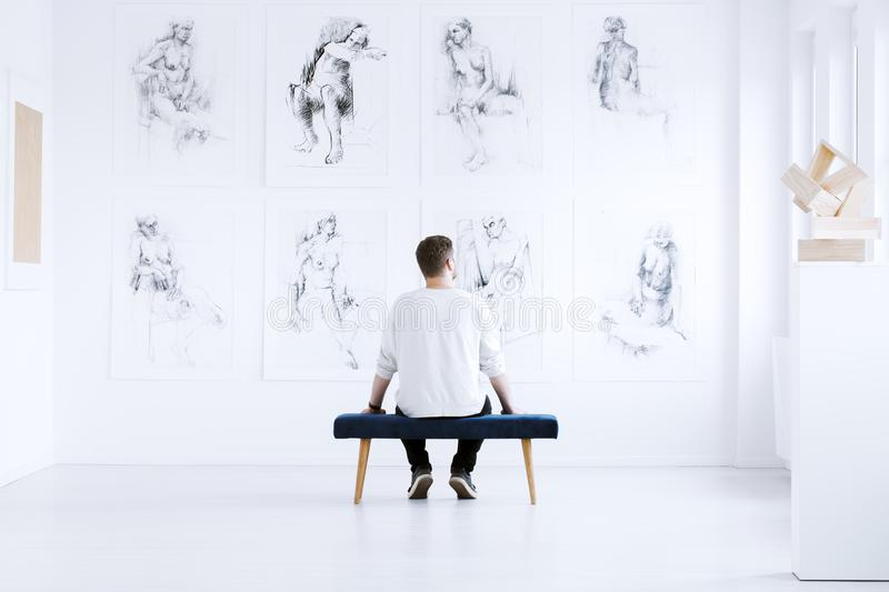 Man relaxing in art gallery royalty free stock photos