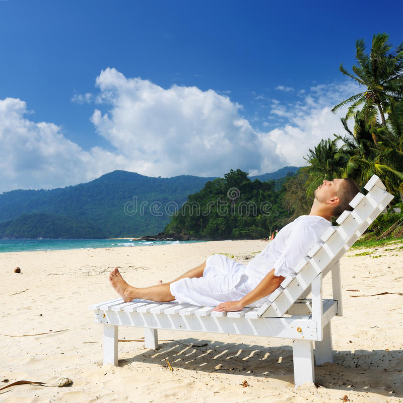 Man relaxing on a beach. Man in white relaxing on a tropical beach royalty free stock image