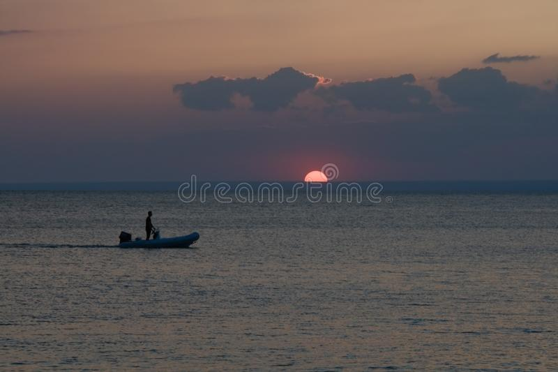 Man relaxing on a boat at Sunset. A man relaxing on a boat at the Sunset royalty free stock photography