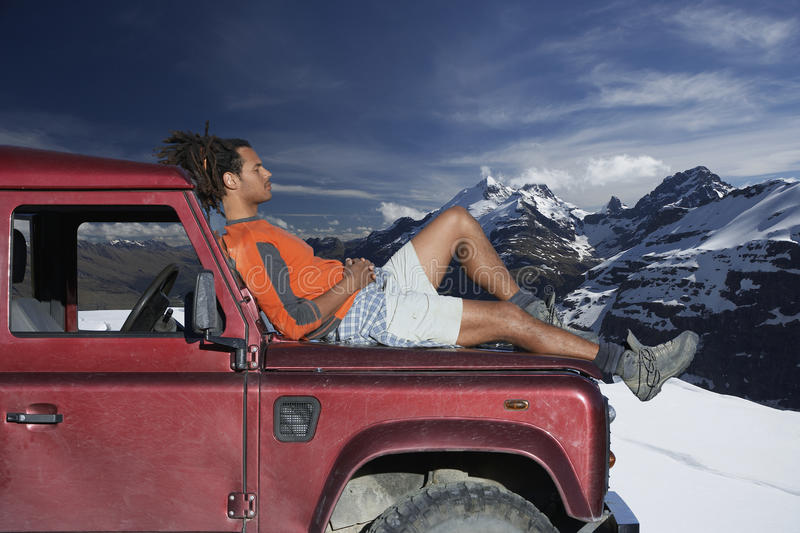 Man Relaxing On Car Hood Against Mountains. Profile shot of man relaxing on car hood against mountains during winter royalty free stock photos