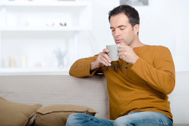 Man relaxing on couch and having tea. Man relaxing on the couch and having a tea stock image