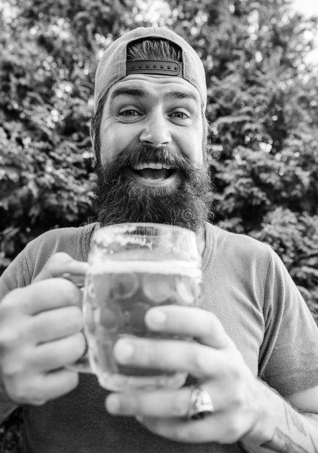 Man relaxing enjoying beer hot summer day. Beer and ale concept. Quench thirst. Hipster brutal bearded man hold mug cold. Fresh beer. Craft beer is young, urban stock photography