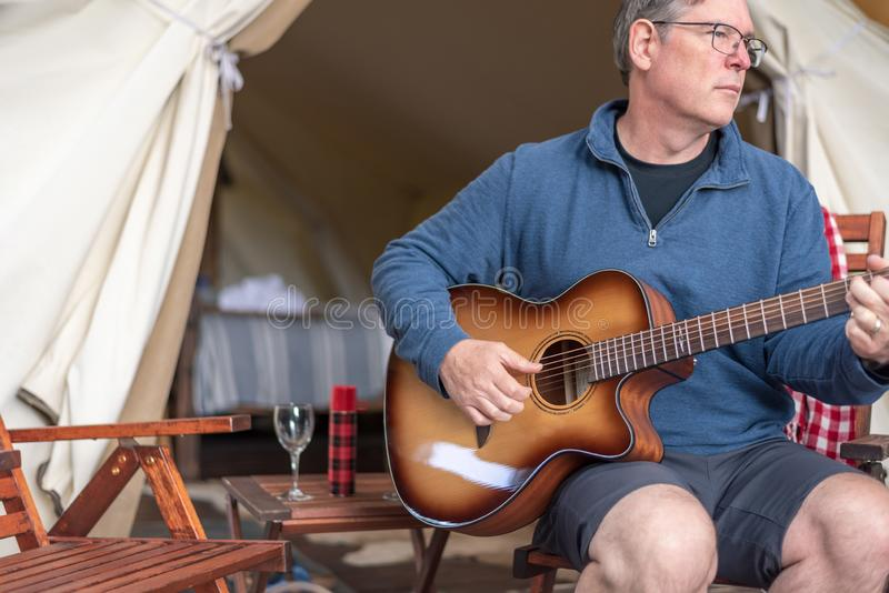 Man relaxing and enjoying some peaceful time playing guitar at the campsite. Man playing guitar at the campsite on vacation royalty free stock photos