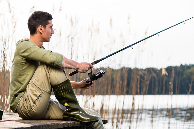 Man relaxing fishing or angling at lake. Sitting cross-legged on jetty royalty free stock photos