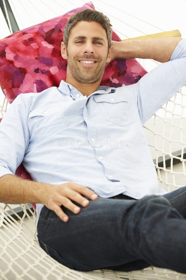 Man Relaxing In Garden Hammock royalty free stock photography