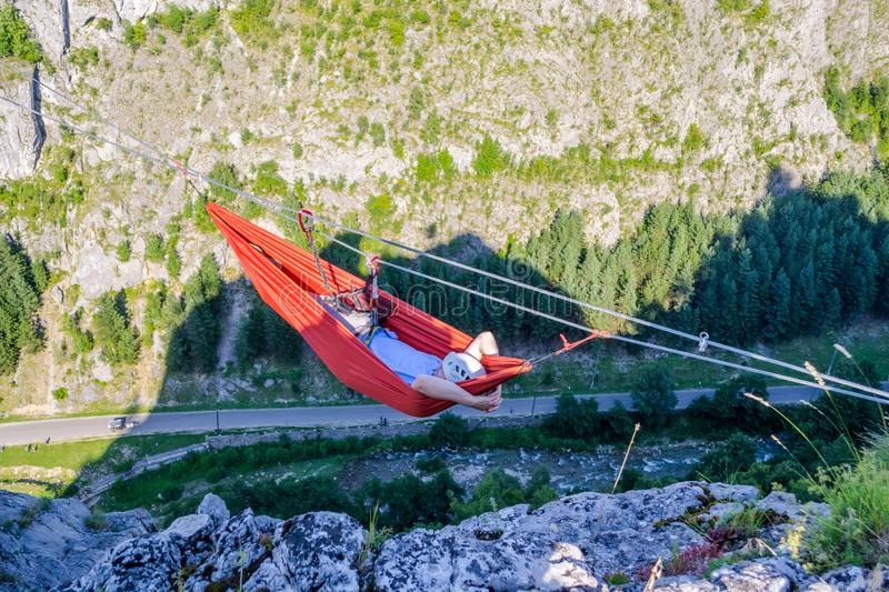 Man relaxing on a hammock set up high on a steel wire, between rock walls, hanging in the air 300 meters above the ground stock images