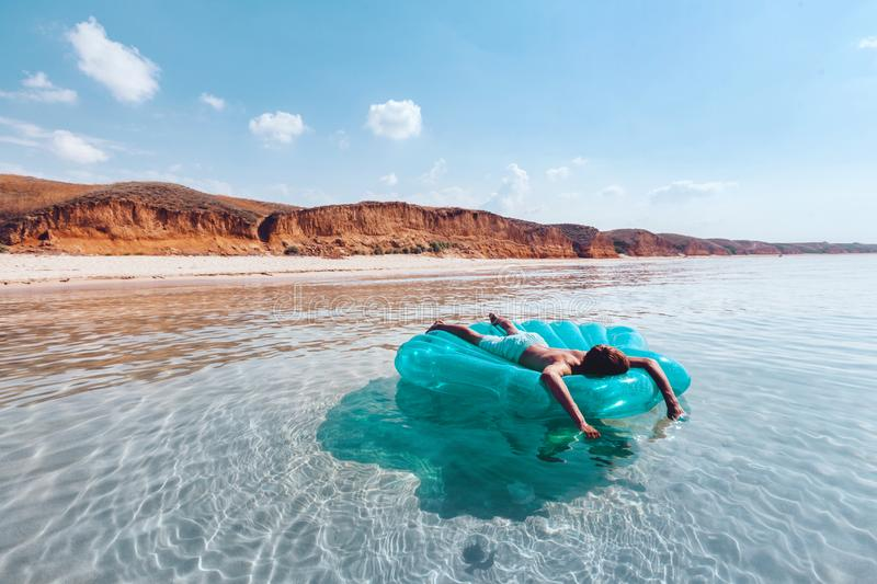 Man relaxing on inflatable ring on the beach royalty free stock image