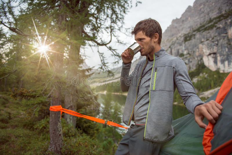 Man relaxing near lake hanging tent camping drinking hot beverage.Group of friends people summer adventure journey in. Mountain nature outdoors. Travel royalty free stock images