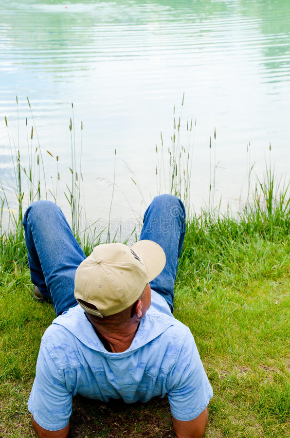 Download Man Relaxing At Pond stock image. Image of male, grass - 20423333