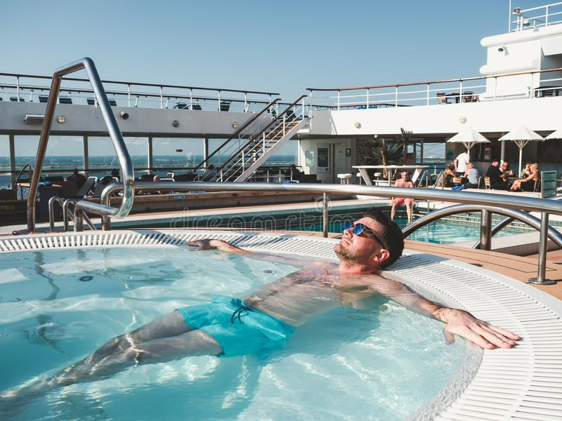 Man relaxing in the pool on the deck stock photos