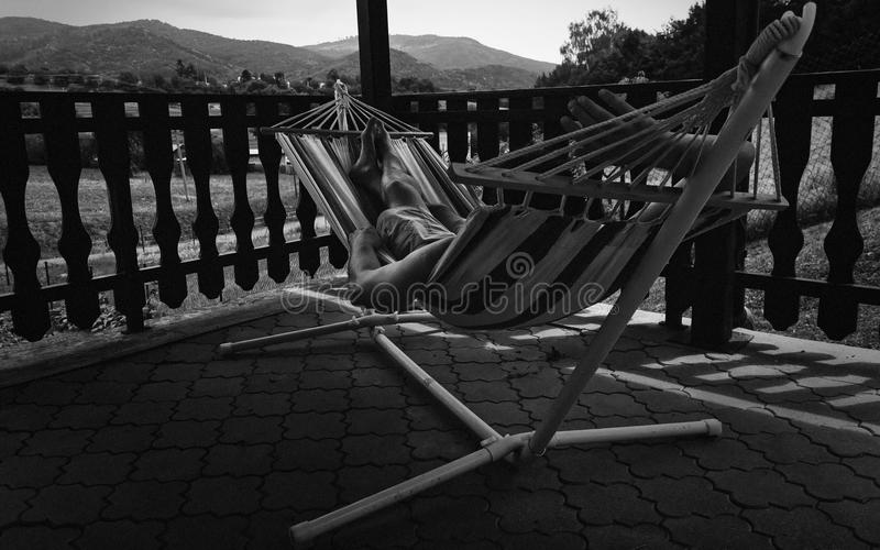 Man Relaxing in Rocking Net on Patio stock photo
