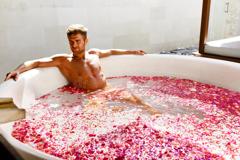 Man Relaxing In Spa Bath With Flowers Outdoors In Day. Man Relaxing In Spa Bath. Beautiful Handsome Healthy Male With Body Bathing, Bathe In Tropical Flower stock image