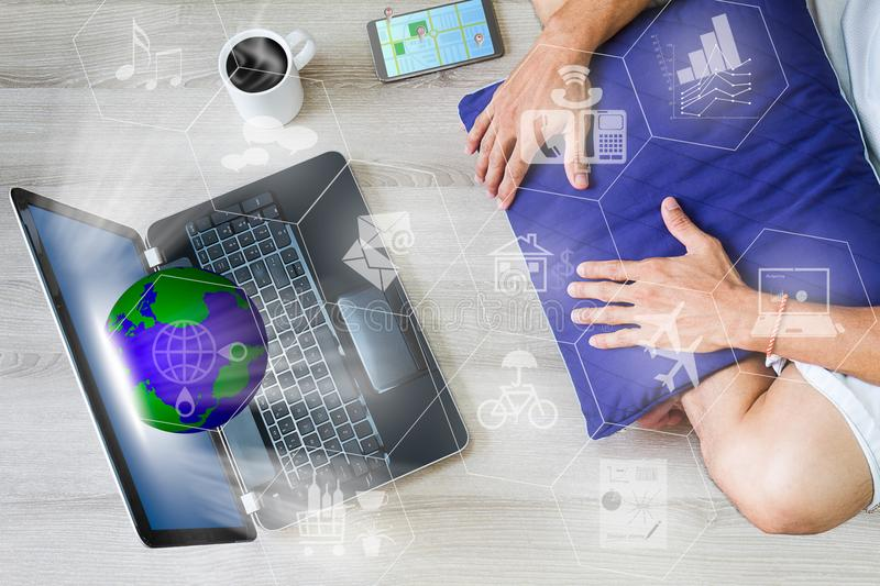 Man relaxing using internet via laptop computer with globe, networks, mobile phone with gps and hot coffee cup on wooden floor royalty free stock photos