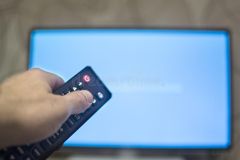 Man with remote control switches channels on the TV, copy paste royalty free stock image