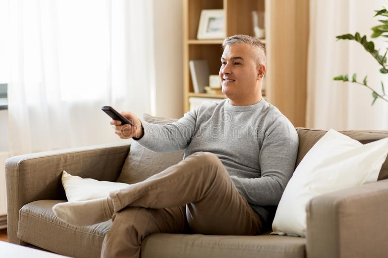 Man with remote control watching tv at home royalty free stock photography