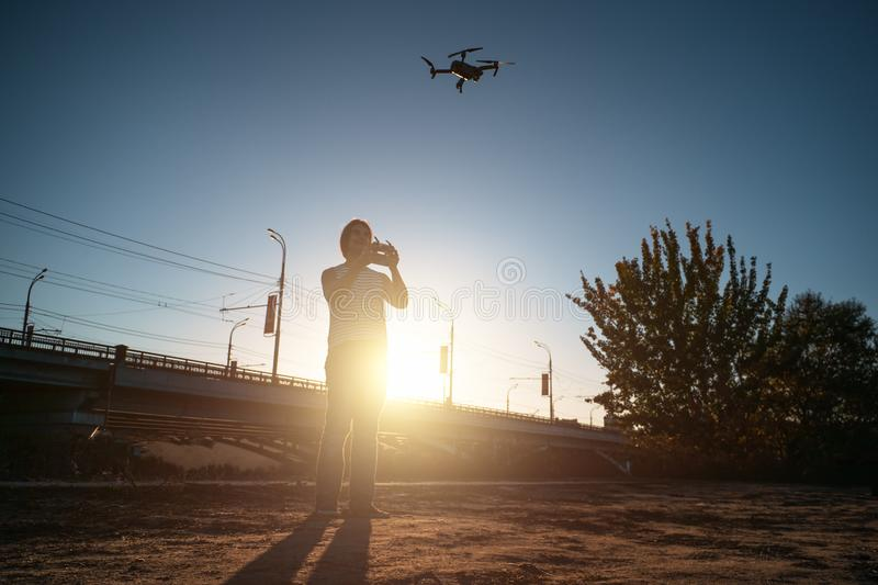 Man with remote controller operating flying drone or quad copter - modern small aircraft for aerial video making in city landscape. At sunset, toned stock images