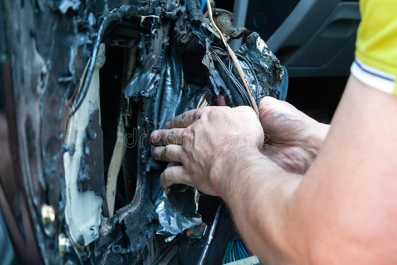 A man removes the door card to find a problem in the inoperative power window and repair it. Car repair at a service station royalty free stock photos