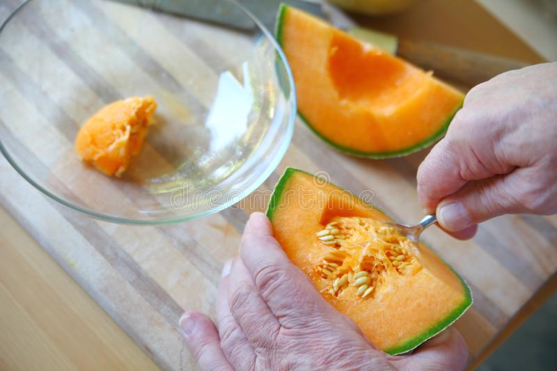 Man removes seeds from cantaloupe closeup stock photo