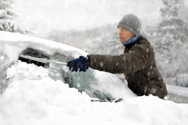 Man removes snow from his car stock image