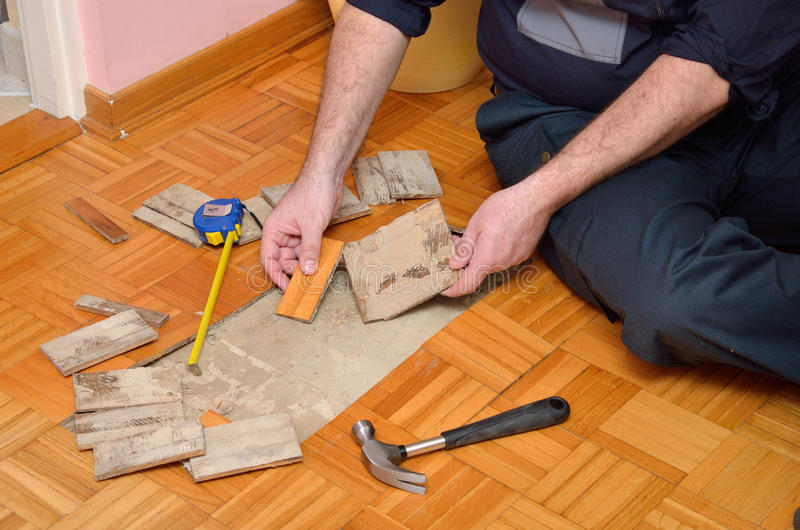 Man Removing Damaged Parquet stock photo