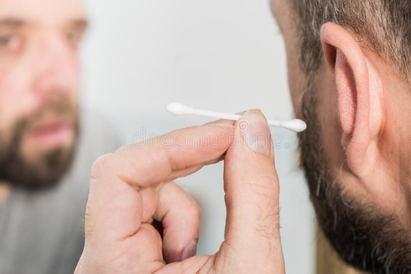 Man removing wax from ear using Q-tip stock photography