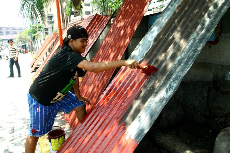 Man repainting used G.I. roofing sheets. Salvaged from a dump site in Manila, Philippines called Smokey Mountain royalty free stock image