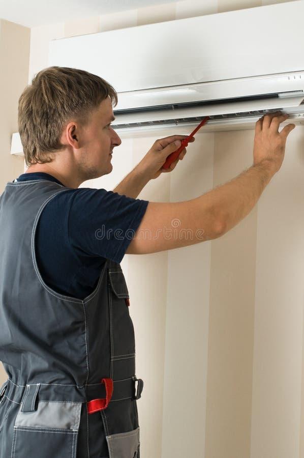 Man repair air-conditioner royalty free stock image