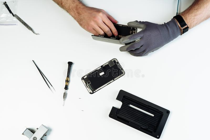Man repair disassembled broken smartphone flat lay royalty free stock photography