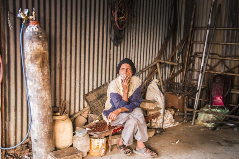 Man in repair shop. A man sitting in a ramshackle repair shop stock photography