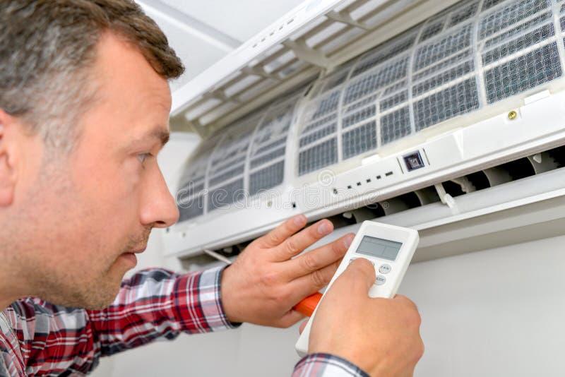 Man repairing air conditioning unit. Activity royalty free stock photos