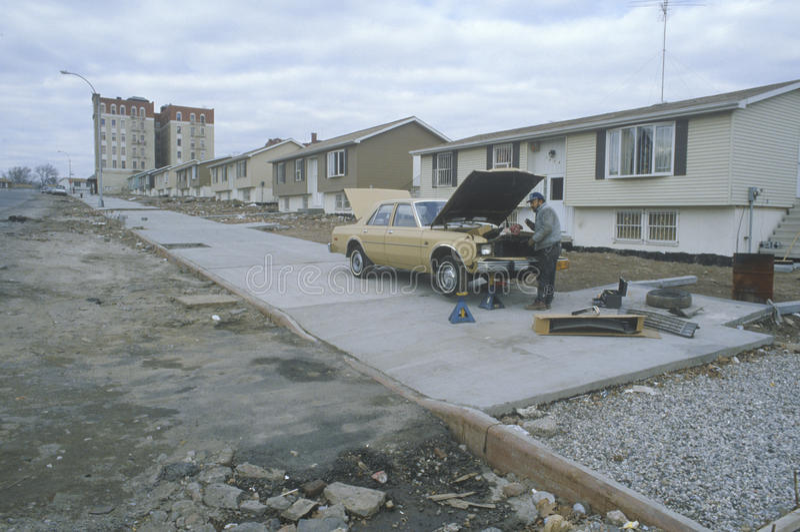 Man repairing car in poor neighborhood,. South Bronx, New York royalty free stock photography