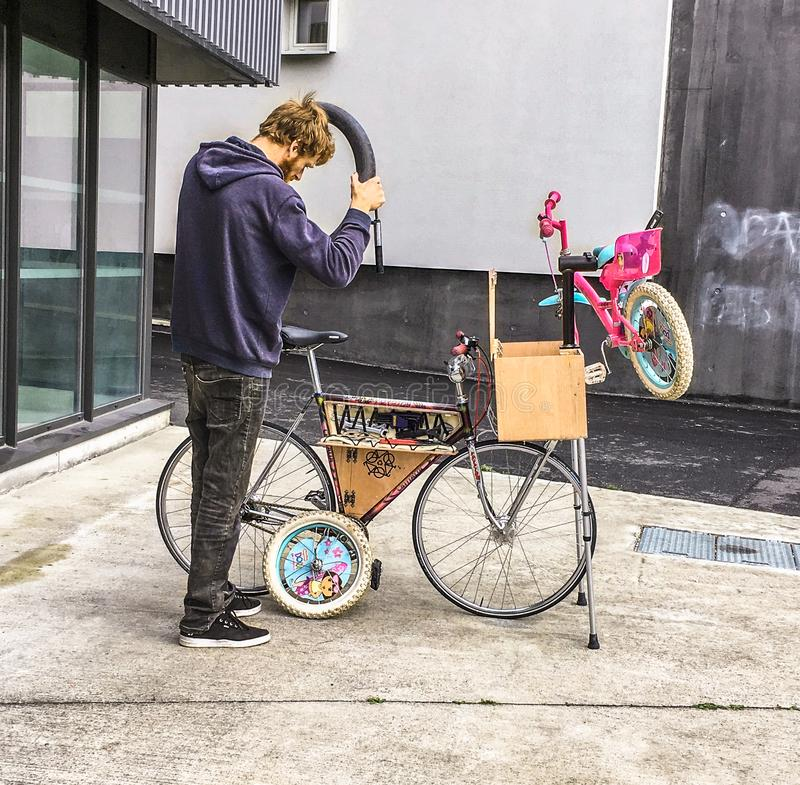 Man repairing a child`s bike on a mobile bicycle repair unit royalty free stock photo