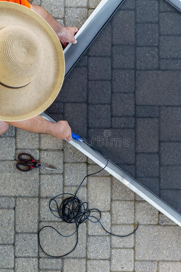 Man repairing a damaged screen door on a patio. After a storm fitting the new wire mesh into the metal frame viewed from above wearing a straw sunhat stock photography