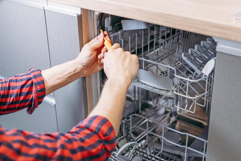 Man repairing dishwasher. Male hand with screwdriver installs kitchen appliances royalty free stock photo