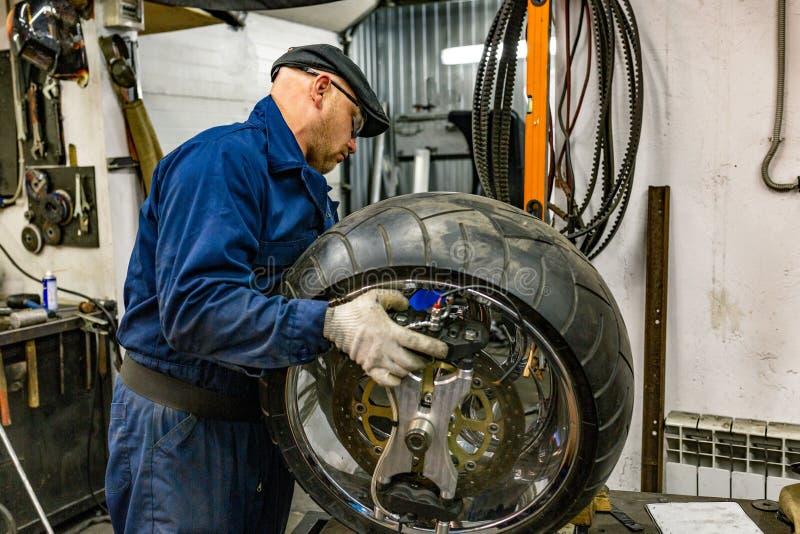 Man repairing motorcycle tire with repair kit, Tire plug repair kit for tubeless tires. The man repairing motorcycle tire with repair kit, Tire plug repair kit royalty free stock image