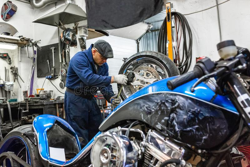 Man repairing motorcycle tire with repair kit, Tire plug repair kit for tubeless tires. The man repairing motorcycle tire with repair kit, Tire plug repair kit royalty free stock photo