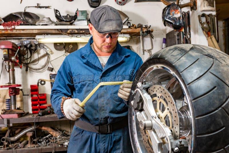 Man repairing motorcycle tire with repair kit, Tire plug repair kit for tubeless tires. The man repairing motorcycle tire with repair kit, Tire plug repair kit stock photography
