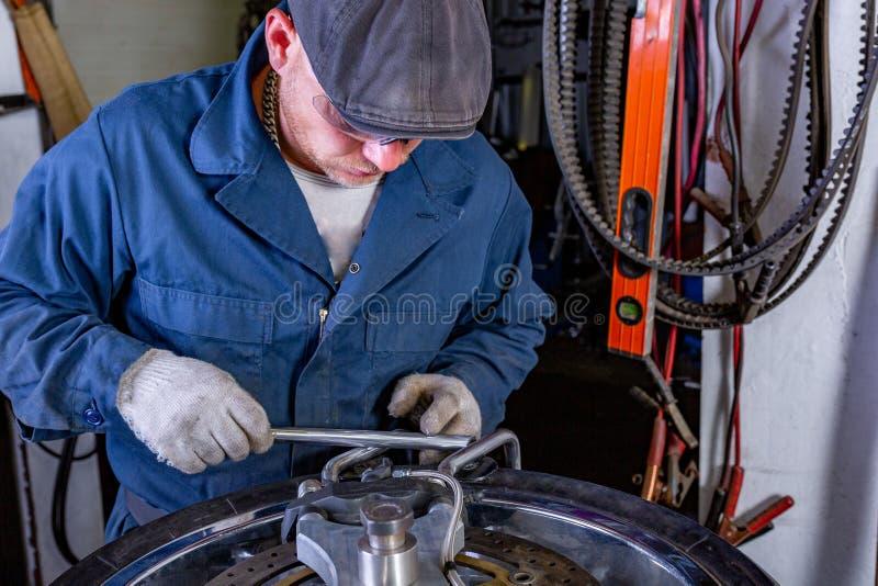 Man repairing motorcycle tire with repair kit, Tire plug repair kit for tubeless tires. The man repairing motorcycle tire with repair kit, Tire plug repair kit royalty free stock photography